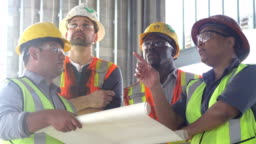 Group of construction workers looking at plans