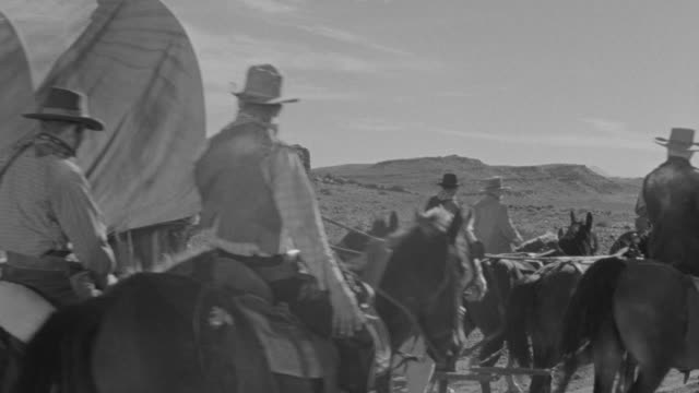 MS PAN Group of cowboys moving with hoarse pulling covered wagons through rural area / Unspecified
