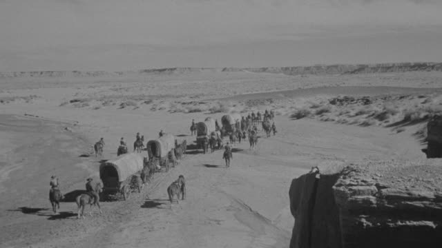 vídeos de stock, filmes e b-roll de ws group of cowboys moving with hoarse pulling covered wagons through rural area / unspecified  - explorador