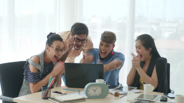 group of coworkers cheering and celebrating success in a office,slow motion - four people stock videos & royalty-free footage