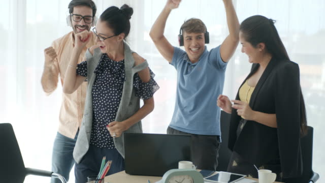 group of coworkers dancing and celebrating success in a office,slow motion - four people stock videos & royalty-free footage