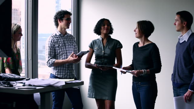 MS Group of coworkers standing in discussion at workstation in office/Washington, USA
