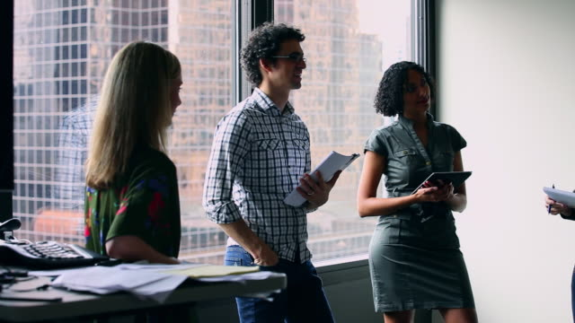 ms pan group of coworkers standing in discussion at workstation in office/washington, usa - note pad stock videos & royalty-free footage