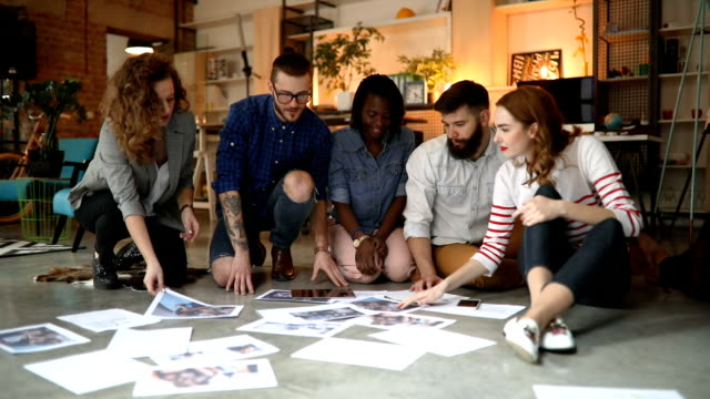 Group of creative people working on floor in office