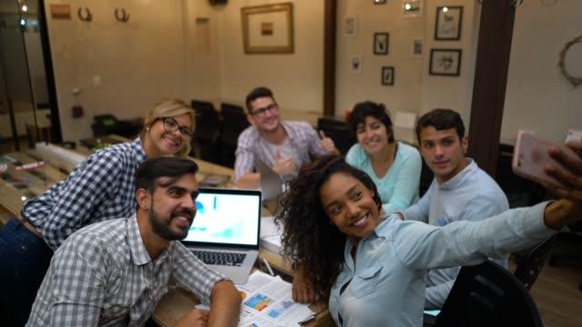 vídeos de stock, filmes e b-roll de grupo de criativos em uma reunião e depois tomar um selfie com um smartphone sorrindo - coworking space
