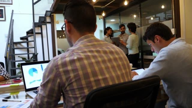 vídeos de stock, filmes e b-roll de grupo de criativos trabalhando em um escritório alguns trabalhando em grupos e outros fazendo suas tarefas individuais - coworking space