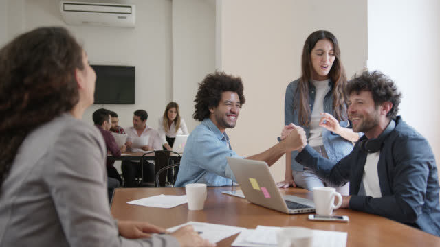 group of creatives working together at a coworking office and business partners shaking hands while discussing an idea - emotion stock videos & royalty-free footage