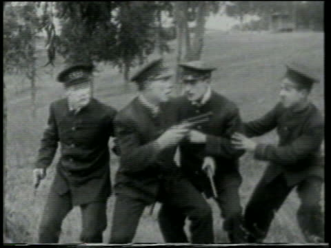 stockvideo's en b-roll-footage met b/w 1915 group of dazed keystone kops with guns looking up at something offscreen / feature - 1915
