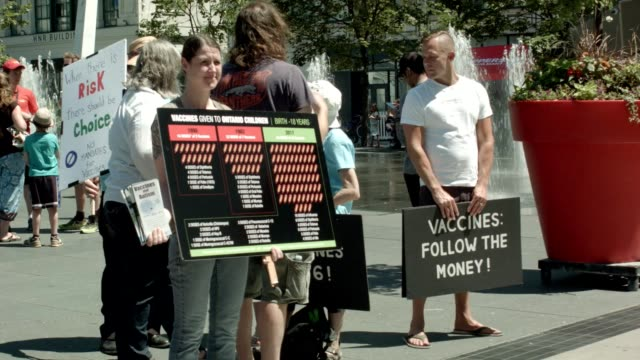 stockvideo's en b-roll-footage met a group of demonstrators at yongedundas square in toronto protest vaccination mandates in the province of ontario - inenting