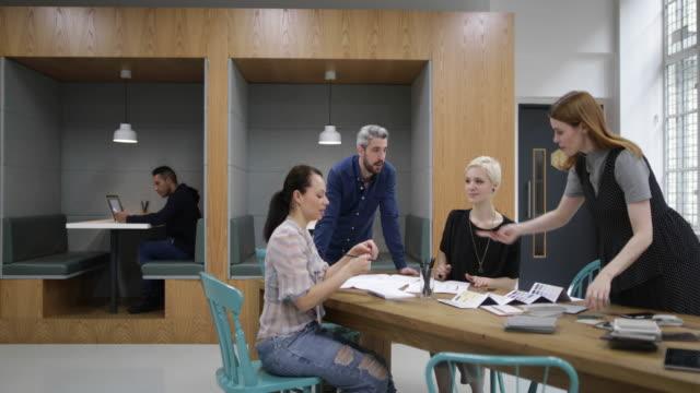 stockvideo's en b-roll-footage met group of designers looking at samples in a meeting - klein kantoor