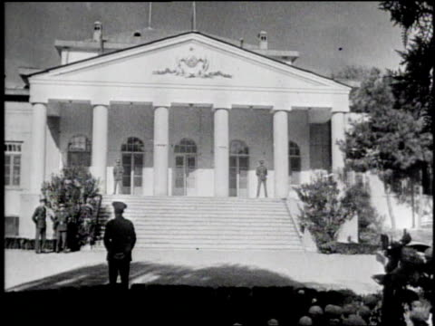 group of dignitaries sitting at long table / exterior of building with guards in front / stalin, roosevelt and churchill sitting in front of building... - 1943 stock-videos und b-roll-filmmaterial