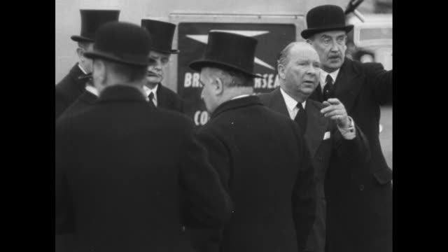 Group of dignitaries stands on tarmac at London airport awaiting arrival of QueenÕs plane / prime minister Winston Churchill walks among group stops...
