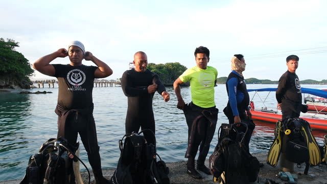 group of divers putting on wetsuits to go scuba diving at hundred islands national park in alaminos, ilocos region, philippines, on friday, september... - aqualung diving equipment stock videos & royalty-free footage