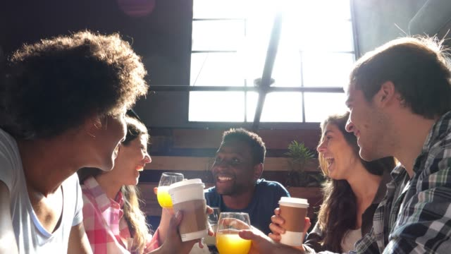 group of diverse friends at a cafe laughing and making a toast with juices and coffee to go - take away food stock videos & royalty-free footage