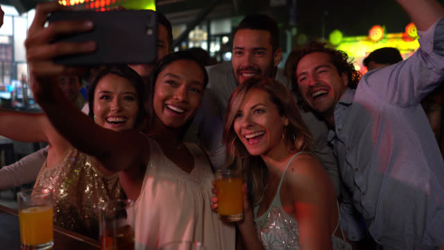group of diverse friends having fun at a bar drinking cocktails and taking a selfie - romance stock videos & royalty-free footage