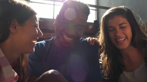 vídeos y material grabado en eventos de stock de grupo de diversos amigos mirando las redes sociales en una tableta riendo y bromeando - cotilleo