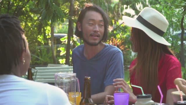 晴れた日にお互いに話し合っている多様な友達のグループ - party hat点の映像素材/bロール