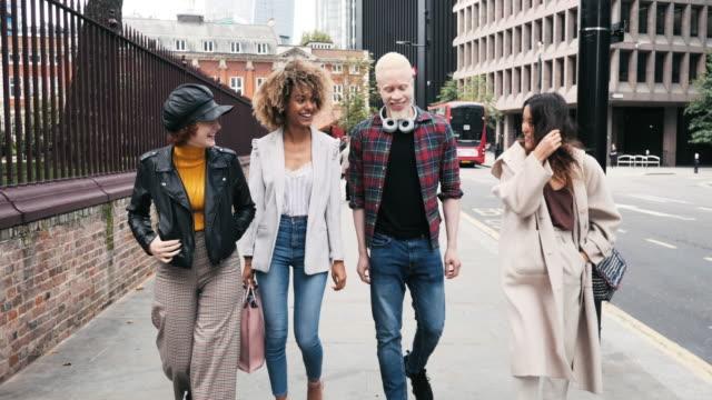 vídeos de stock, filmes e b-roll de grupo de millennials diversos que andam abaixo da rua - aço