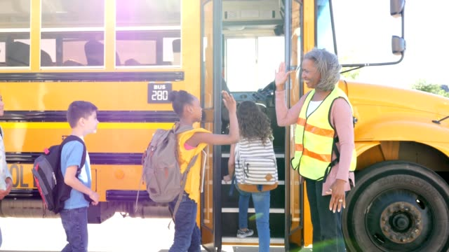 group of diverse mixed aged school children board school bus - moving toward stock videos & royalty-free footage