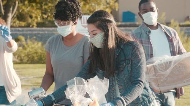 group of diverse people volunteer during food drive - volunteer stock videos & royalty-free footage