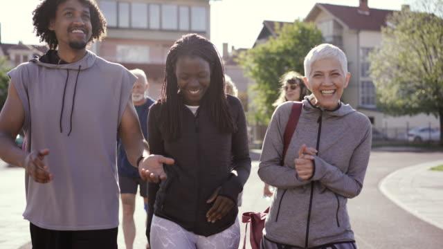 vidéos et rushes de groupe de personnes diverses marchant ensemble et parlant après leur cours de danse - s'impliquer à fond