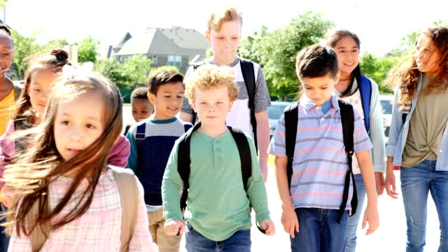 group of diverse schoolchildren walking up to the school building - first day of school stock videos & royalty-free footage