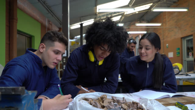 vídeos de stock, filmes e b-roll de grupo de alunos diversos durante oficina de carpintaria planejando um projeto discutindo e tomando notas - protetor de ouvido