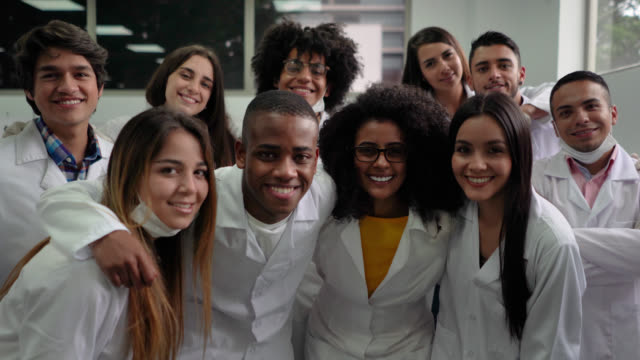 group of diverse students during science class wearing lab coats, protective gloves and masks smiling at camera - human age stock videos & royalty-free footage