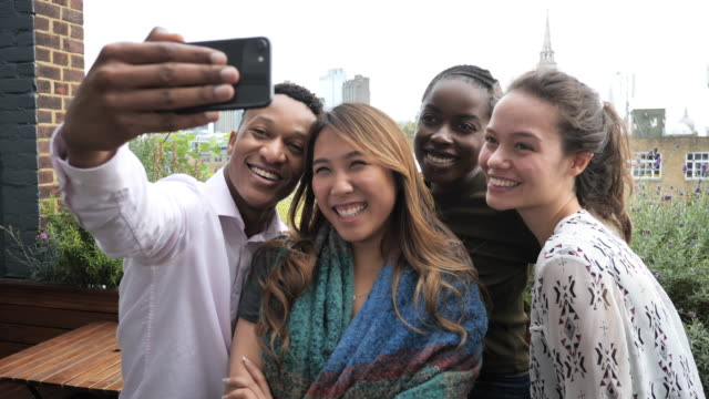 group of diverse young people taking selfie and laughing - mixed age range stock videos & royalty-free footage
