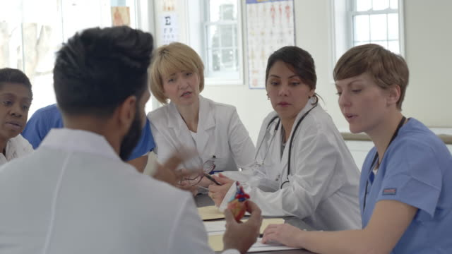 group of doctors sitting around a table - comforting colleague stock videos & royalty-free footage