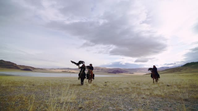 group of eagle hunters near the river in mongolia - mongolia video stock e b–roll