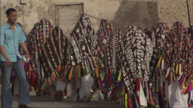 a group of egyptian women in matching ceremonial dress walk down a busy city street, swinging their brightly colored shawls. - モデスト・ファッション点の映像素材/bロール