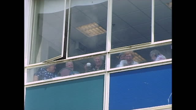 group of elderly ladies laugh and drink hot drinks as they watch the pride parade as it passes the building in which they are sitting, brighton, uk;... - adult stock videos & royalty-free footage
