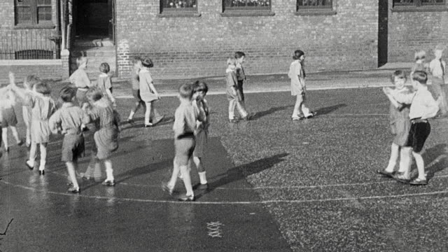 1925 ws group of elementary boys and girls performing a dance routine as couples on the playground / newcastle upon tyne, england, united kingdom - 1925年点の映像素材/bロール