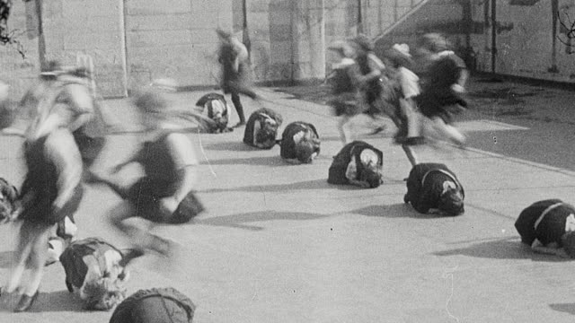 1925 montage group of elementary schoolgirls dressed in gymslips performing calisthenics on playground / newcastle upon tyne, england, united kingdom - 1920 stock-videos und b-roll-filmmaterial