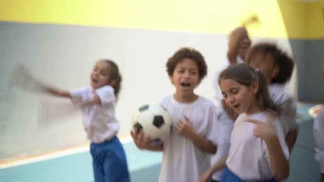vídeos de stock, filmes e b-roll de grupo de alunos do ensino fundamental celebrando em quadra esportiva na escola - 8 9 anos