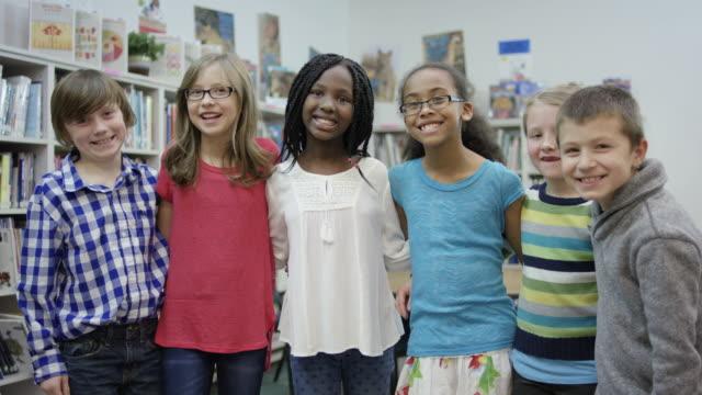 eine gruppe von elementaren schülern posieren zusammen in der bibliothek - gemischte altersgruppe stock-videos und b-roll-filmmaterial