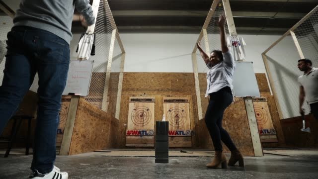 stockvideo's en b-roll-footage met a group of employees from capitol one throw hatchets during a team building event at bad axe throwing march 28 2018 in washington dc axe throwing is... - bijl