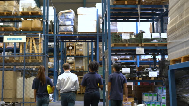 group of employees walking in warehouse - foreman stock videos & royalty-free footage