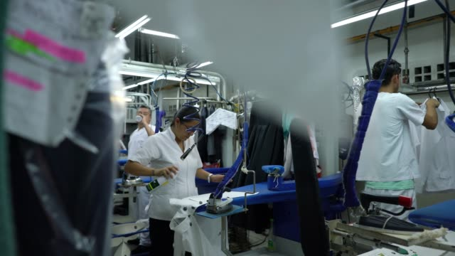 group of employees working at an industrial laundry service ironing clothes - launderette stock videos & royalty-free footage