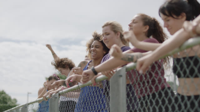 slow mo. group of energetic women dance together on a set of bleachers at the end of their exercise session - zaun stock-videos und b-roll-filmmaterial