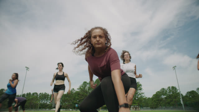 slo mo. group of energetic women run drills on an american football field and one woman glares into the camera - sweat stock videos & royalty-free footage