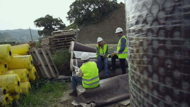 MS POV Group of engineers discussing plans on construction site, surrounded by rolls of geotextile material / Malaga, Andalusia, Spain