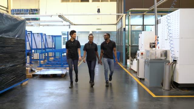 stockvideo's en b-roll-footage met groep ingenieurs die het werk bespreken terwijl het bewegen in fabriek - auto industrie