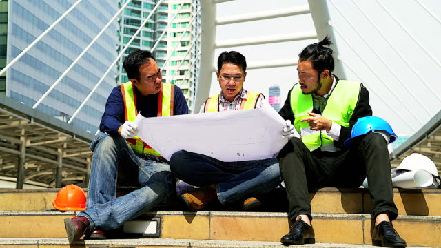 Group of Engineers meeting at terrace on top of construction site. Coworkers discussing. Boss and worker argue. Conversation in team.wear helmet hold paper plans