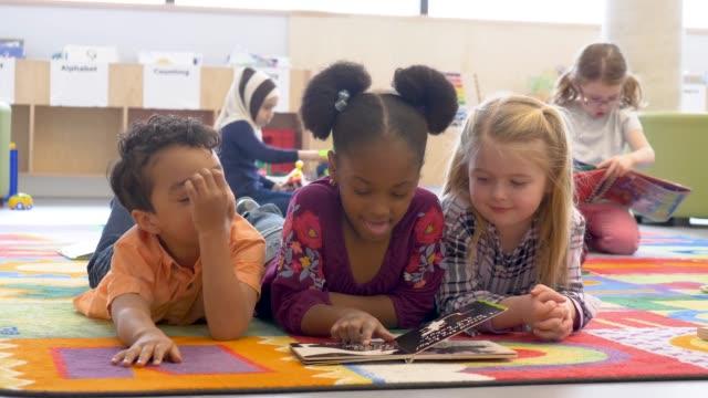 vídeos de stock, filmes e b-roll de grupo de miúdos étnicos na leitura da creche - escola