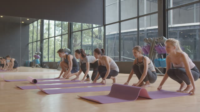 group of ethnically diverse people rolling black fitness or yoga mat before yoga class - classroom stock videos & royalty-free footage