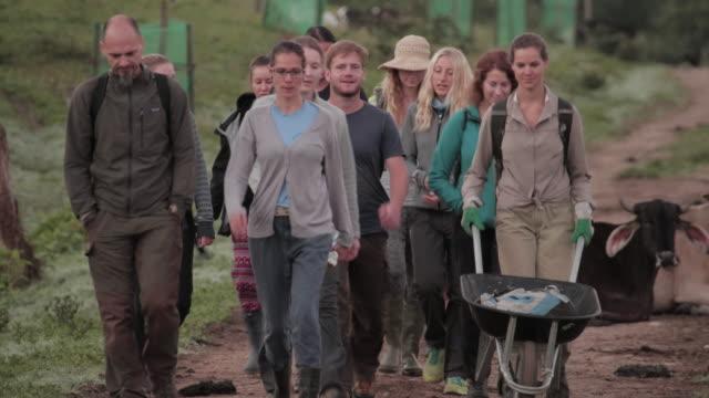 vídeos y material grabado en eventos de stock de grupo de voluntarios de la granja caminando por un camino de tierra - voluntario