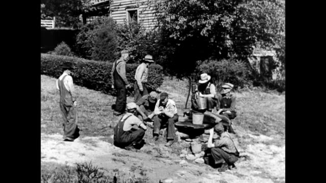 group of farmers sitting on the grass outside farmhouse resting and talking about electricity / man points to the sky discussing electricity pylons... - agricultural cooperative stock videos and b-roll footage