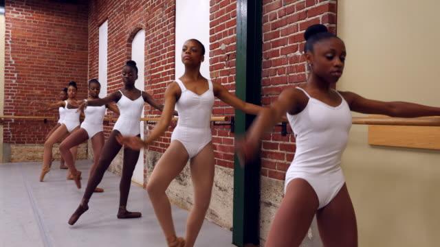ms group of female ballet dancers practicing at barre in studio - バレエ練習用バー点の映像素材/bロール